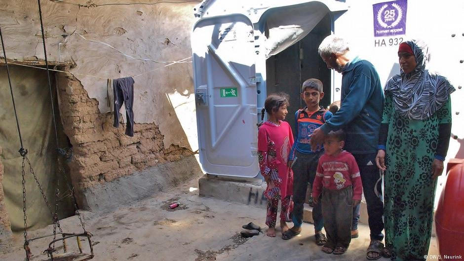 An Iraqi family in front of their partially destroyed house
