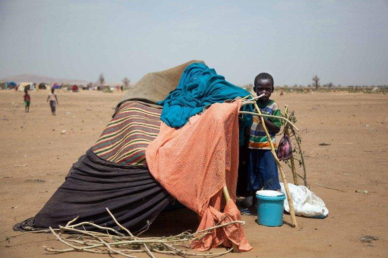 Un enfant soudanais se tient devant son abri au camp de Kalma (Sud-Darfour) de l'ONU, le 9 mars 2014. Crédit : AFP