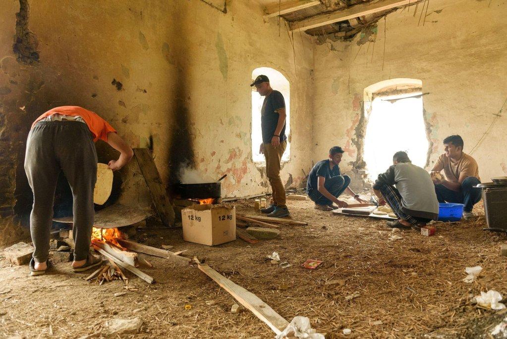 ansa / مهاجرون يخبزون ويطهون في عقار مهجور بضواحي هورغوس في شمال صربيا، بالقرب من الحدود المجرية. المصدر: إي بي إيه/ إدفارد مولنار.
