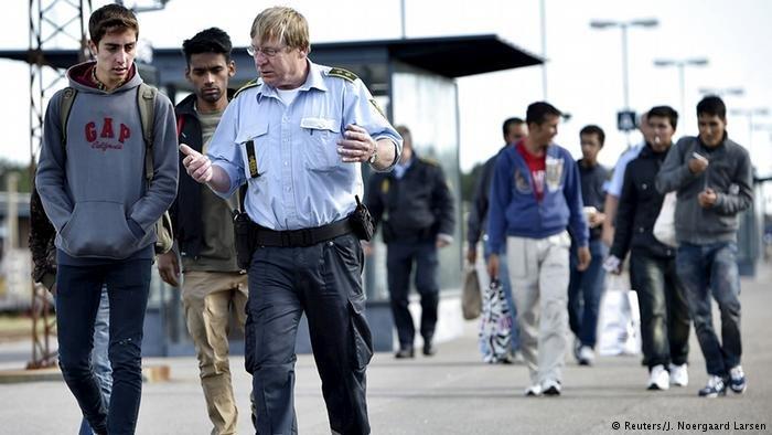 ضابط دنماركي يتكلم مع لاجئ سوري عند وصوله مع بعض اللاجئين إلى الدنمارك (Reuters/J. Noergaard Larsen)