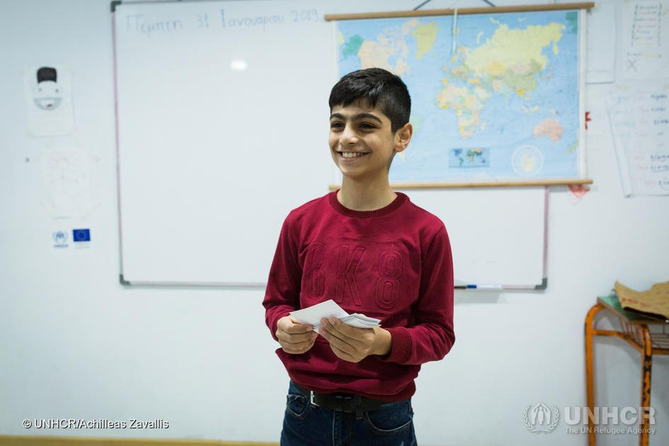 Ali a 12-year-old asylum seeker from Iraq who attends classes at the KEDU school reads the names of different animals from pieces of paper during a word association game  Photo UNHCR  Achileas Zavallis