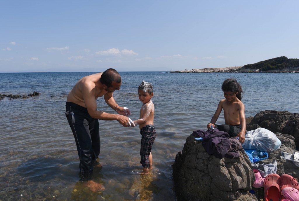 دریا به جای دوش! عظیم، مهاجر افغان که چهار فرزند دارد، سر پسرش مصطفی را با شامپو میشوید.  عکس از مهدی شبیل/ مهاجر نیوز
