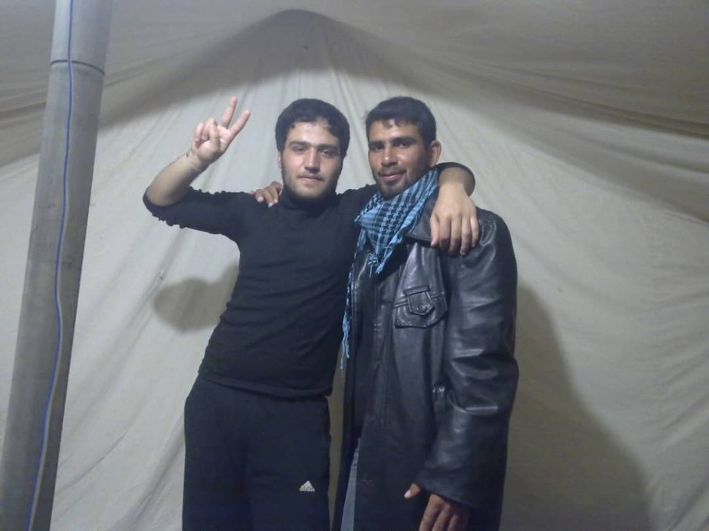 خالد الجزار في مخيم للاجئين مع رفيق له قبيل إصابته.
