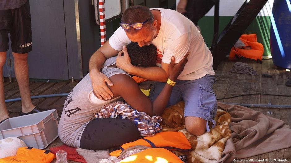 A migrant is comforted by a crew member of the Open Arms Spanish humanitarian boat off the coast of the Sicilian island of Lampedusa southern Italy  Photo Picture-allianceAP PhotosFGentico