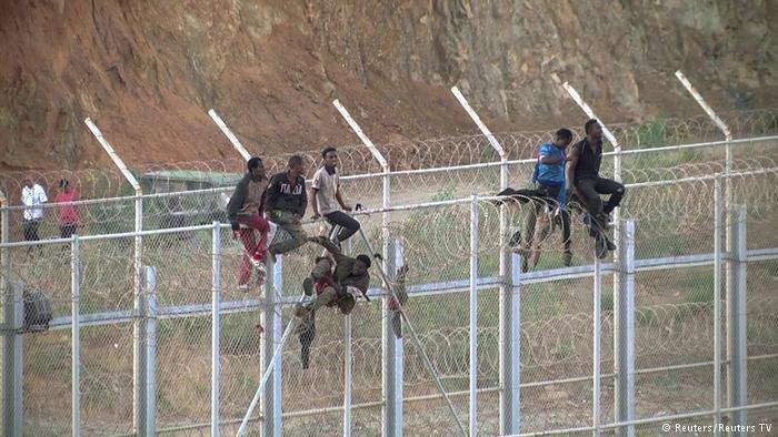 African migrants climb a fence into Ceuta