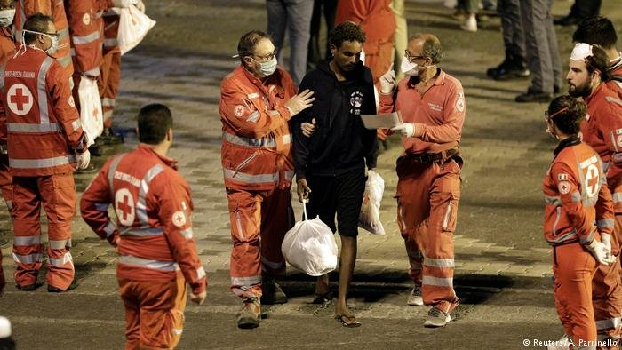 Red Cross workers help a migrant who has disembarked from the Diciotti