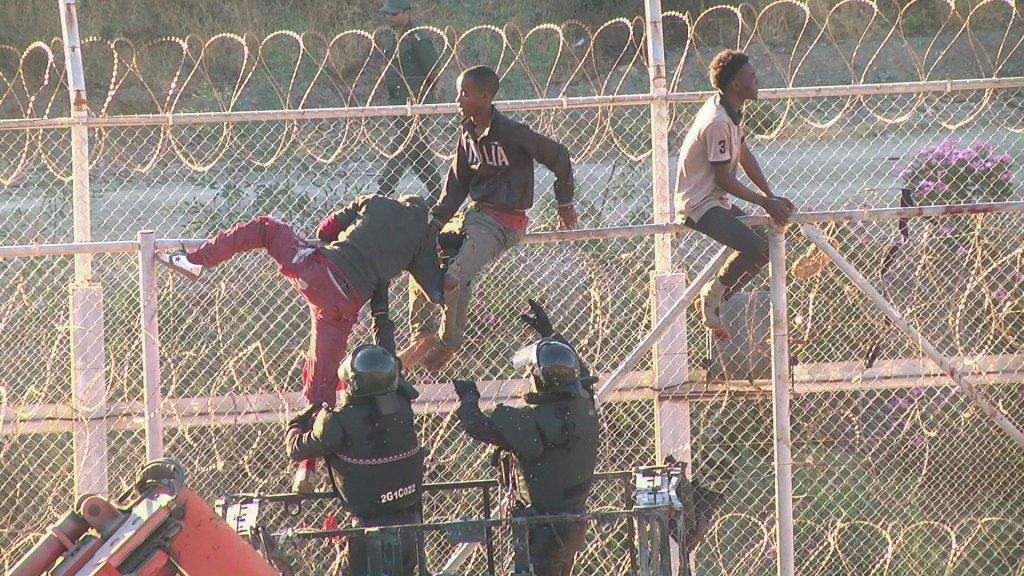 Reuters |Migrants traversant la barrière grillagée entre le Maroc et l'enclave espagnole de Ceuta, le 26 juillet 2018.