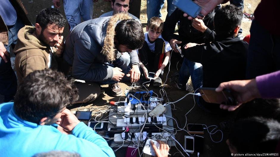 Migrants charge their phones at a camp on the Greek-Macedonian border