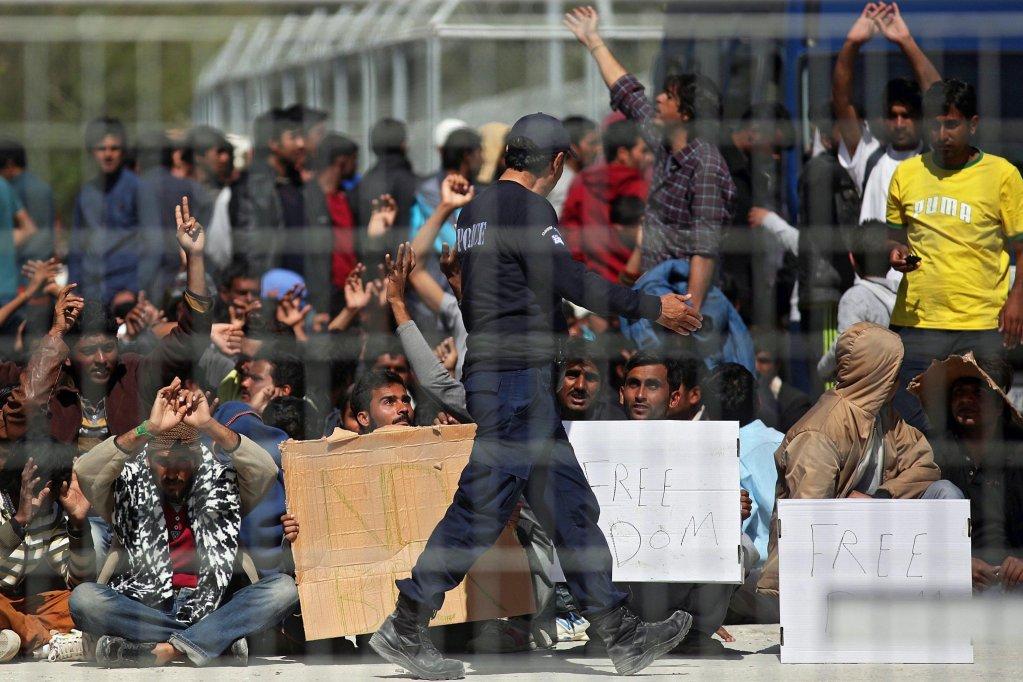 """ansa / مهاجرون من أفغانستان وباكستان، يحتجون ضد ترحيلهم في إحدى النقاط الساخنة في مركز استقبال اللاجئين، الذي كان مركزا للاعتقال في موريا بجزيرة ليسفوس. المصدر: صورة أرشيفية من """"إي بي إيه""""."""