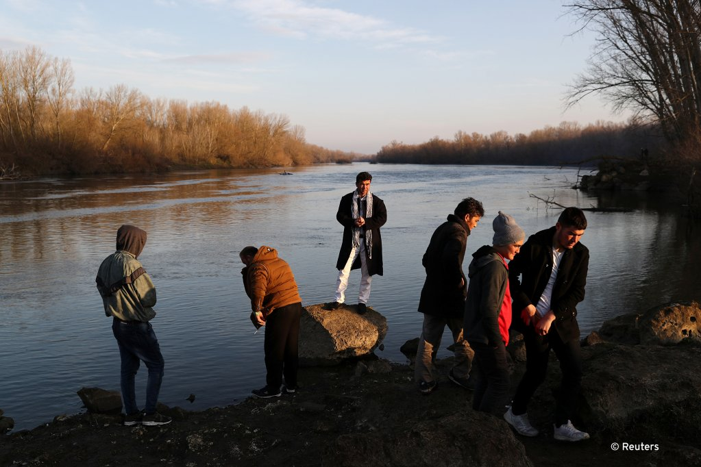 Migrants stand on the banks of Evros river natural border between Turkey and Greece near Edirne Turkey March 2 2020  Photo REUTERSMarko Djurica