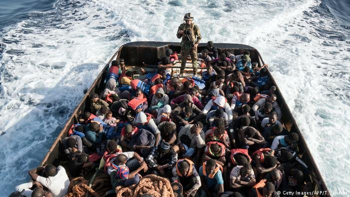 A Libyan coast guardsman stand on a boat crowded with migrants