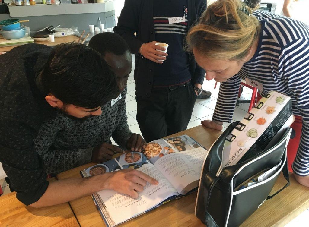 Petra et Alan cherchent une recette dans le livre de Najo. Crédit : Leslie Carretero
