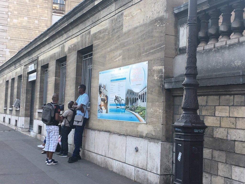 مرضى بانتظار دورهم للدخول إلى مركز الرعاية الصحية أمام مشفى أوتيل ديو في باريس يوم الجمعة 27/07/2018. مهاجرنيوز