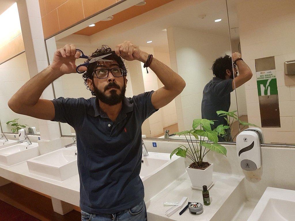 حسان القنطار يحاول قص شعره في أحد حمامات مطار العاصمة الماليزية كوالالمبور في 21 آب/أغسطس 2018. رويترز/حسان القنطار