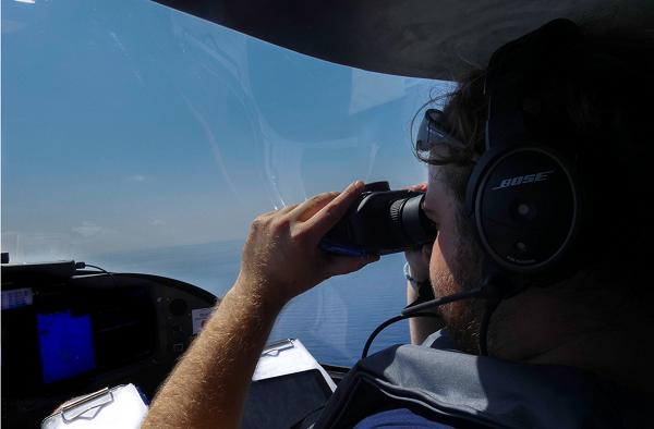 L'équipe des pilotes volontaires tentent de repérer les embarcations de migrants à l'aide de jumelles. Crédit : Pilotes volontaires