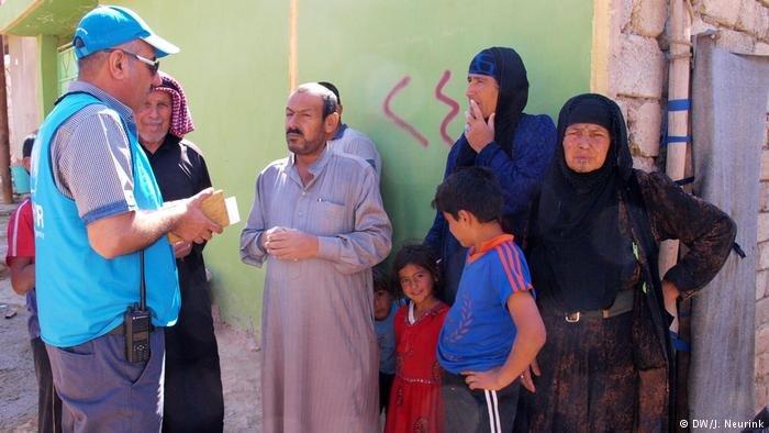 UNHCR representative speaking to migrants   Photo: DW/J.Neurink