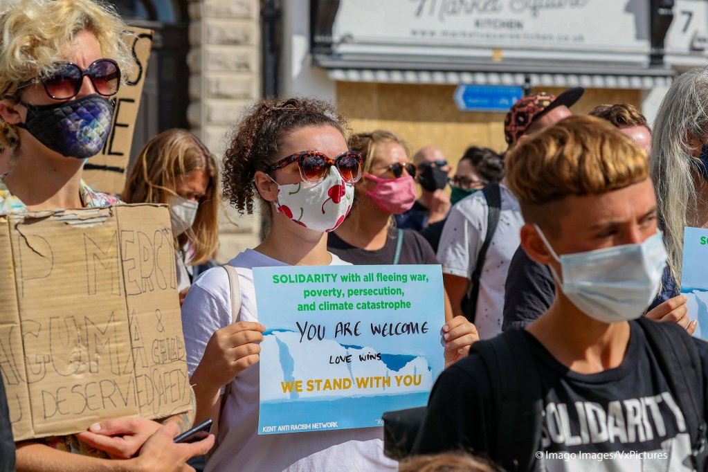 People wearing face protective masks holding pro-refugees and migrants placards are gathered in Market Square in Dover on Saturday Sept 5 2020  Photo IMAGO