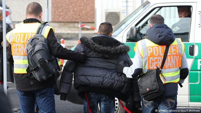 Police officers accompany a failed asylum seeker to Leipzig-Halle airport