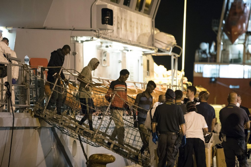 "Migrants disembark from Frontex ship ""Protector"" in the night at the port of Pozzallo, Sicily, Italy. Credit: ANSA/ Francesco Ruta"