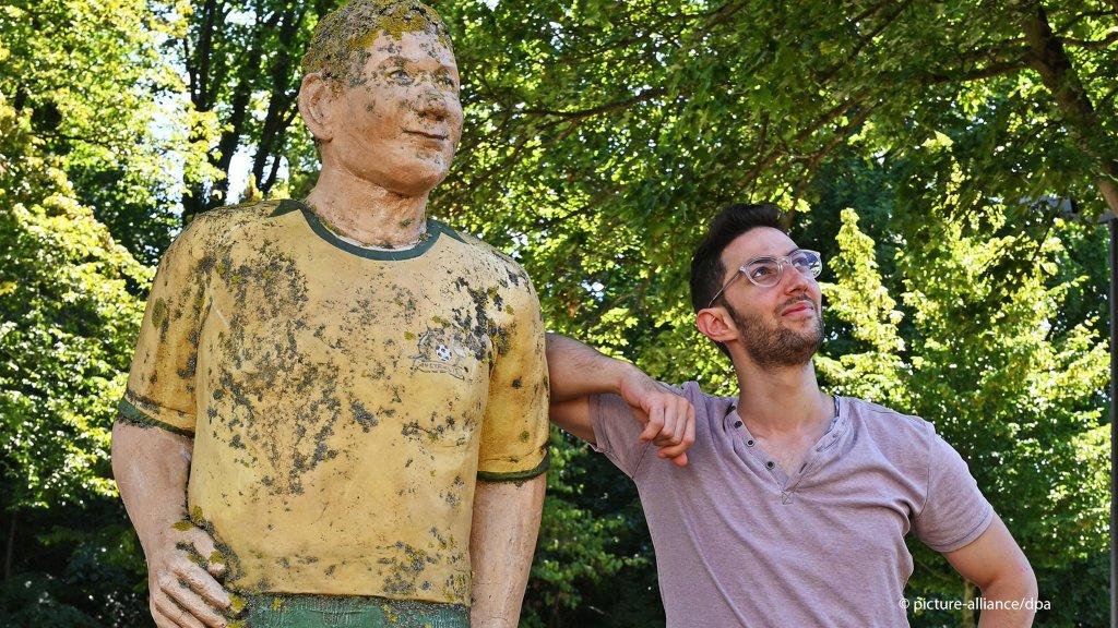 اللاجئ السوري محمد تحسين بيك يقف إلى جانب تمثال يرمز للاعب كرة قدم في مينة كايزرسلاوترن