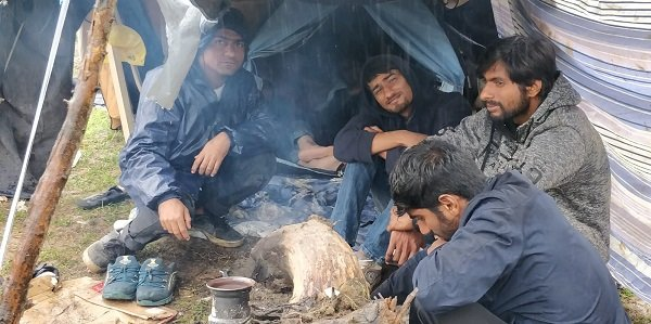 Abdullah au fond avec sa capuche va dormir ce soir au pied dune tente dj bonde sur un couverture  Crdit  InfoMigrants