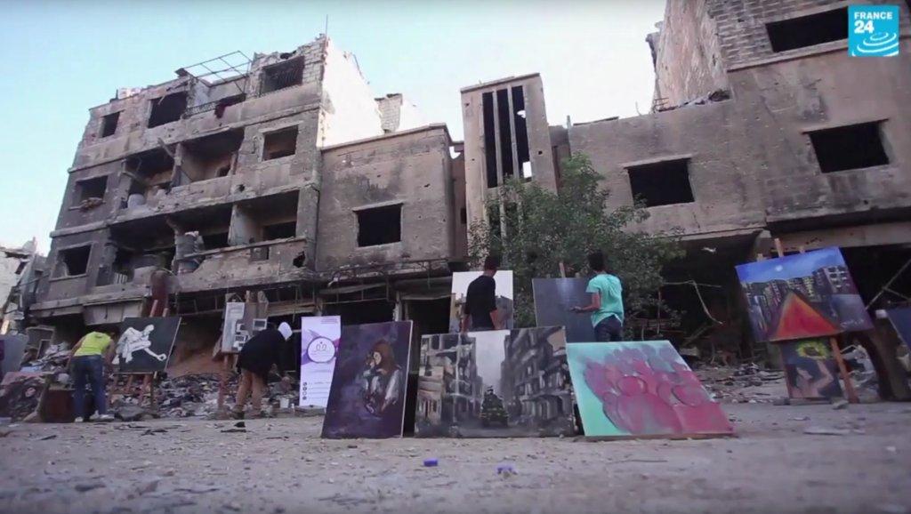 رسامون يحولون إحدى ساحات مخيم اليرموك للاجئين الفلسطينيين إلى مرسم. أ ف ب