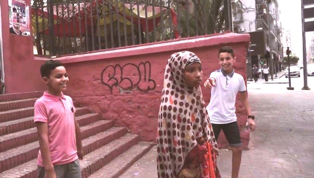 Dans le clip, une jeune fille originaire d'Afrique subsaharienne suscite les moqueries d'enfants algériens. Vidéo Democratoz.