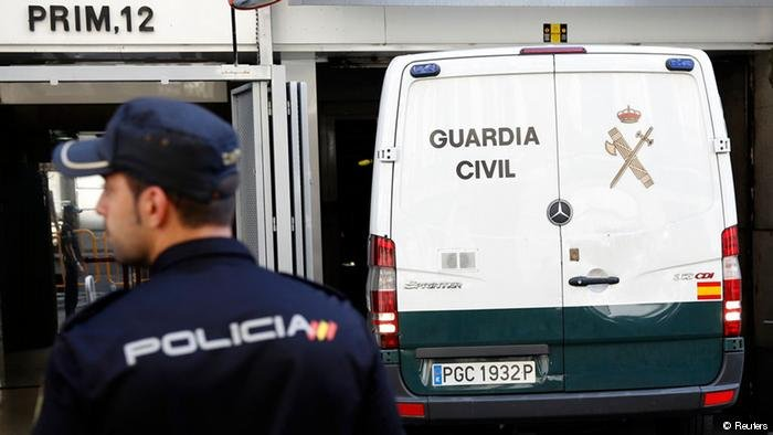 Spanish police officer and a police van | Photo: Reuters