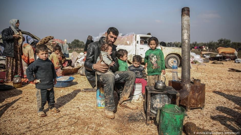 A man sits with his children in front of an oven at a makeshift camp in Idlib Syria  Photo Picture-alliancedpa