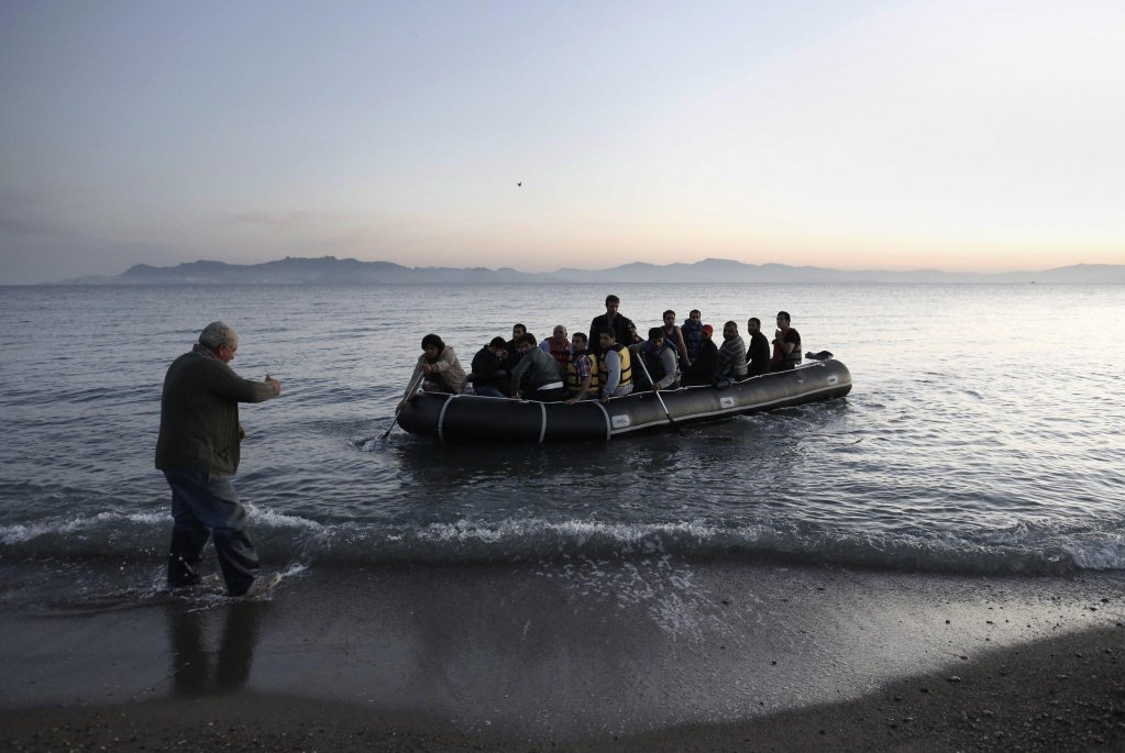 Man trying to help Syrian refugees who were adrift on a dinghy, as they disembark on the coast of Turkey