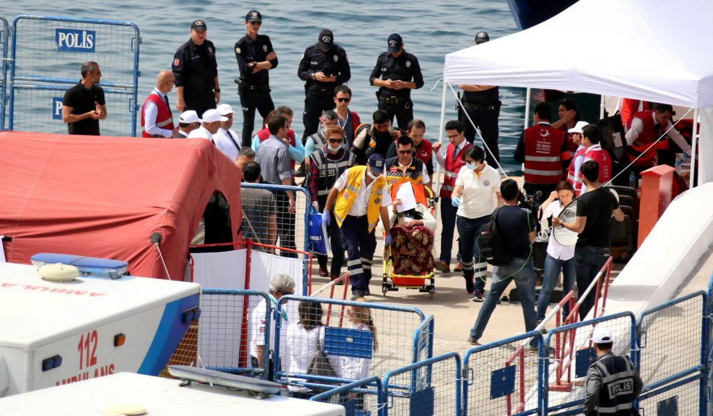Refugees being escorted by Turkish police as they arrive by ferry. PHOTO/EPA/MERT CAKIR