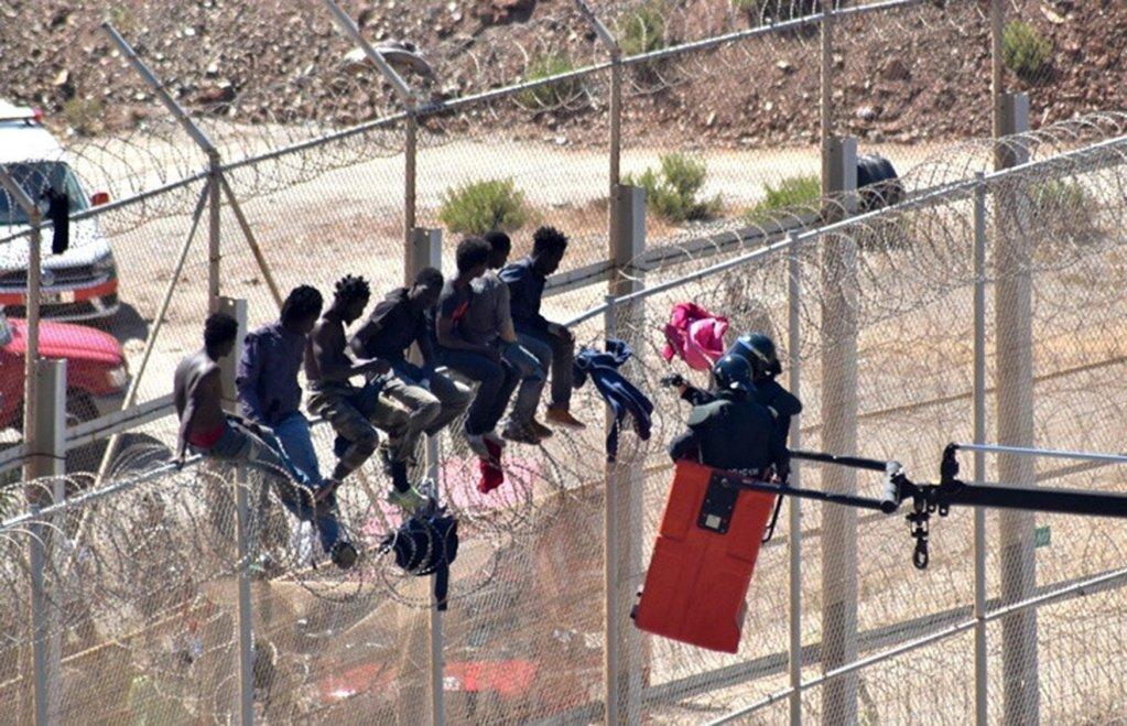 مهاجرون يتسلقون السياج الفاصل بين إسبانيا والمغرب. أرشيف