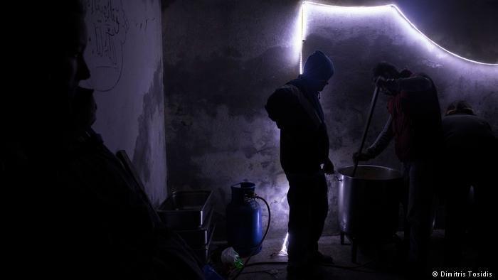 يطبخ مهاجران العشاء للمتجمعين في المصنع المهجور بالقرب من القرية الحدودية. ويعاني مئات طالبي اللجوء من الجوع والمشقة والإصابات والعنف اليومي وهم يحاولون البقاء على قيد الحياة