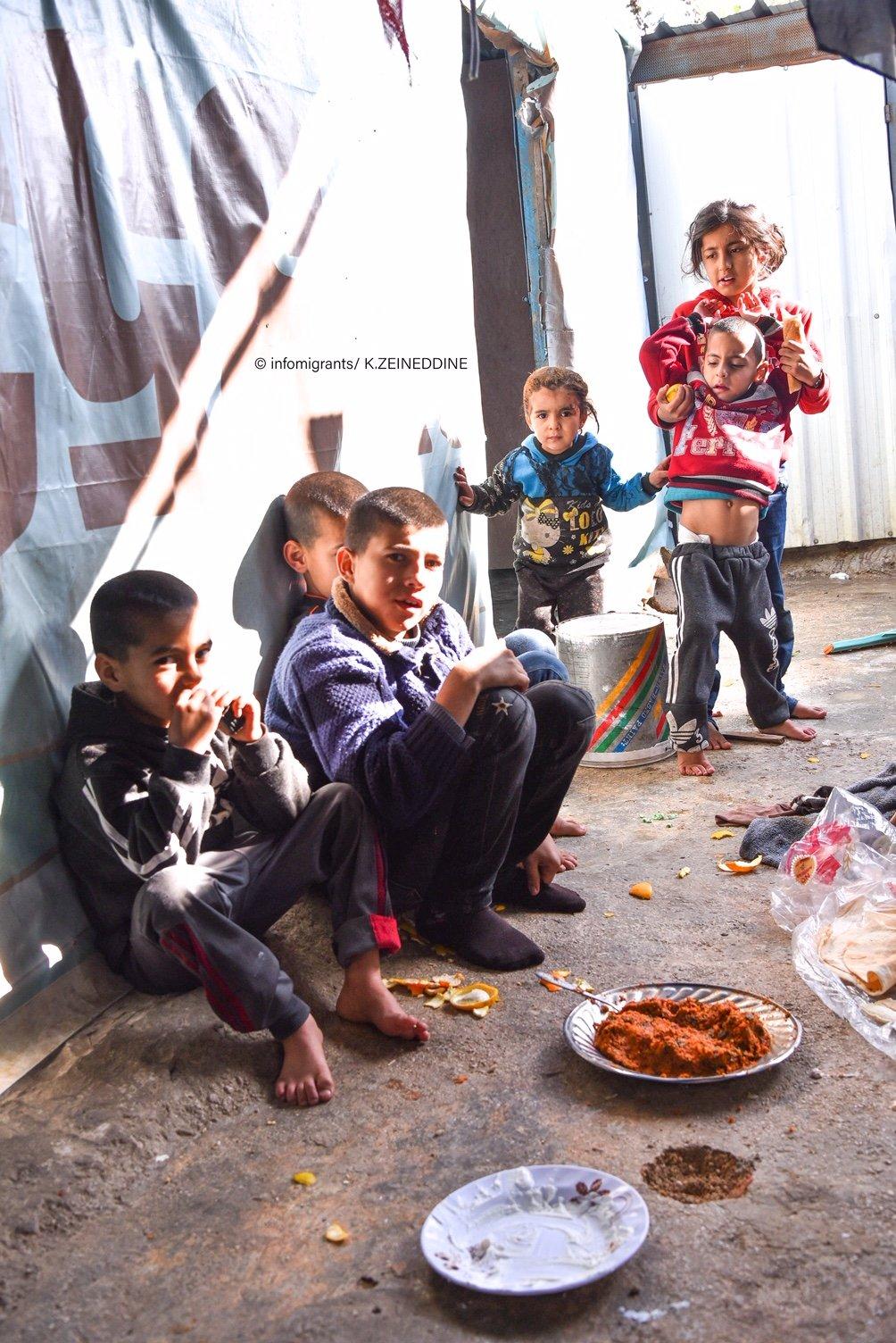 يتناولون الغذاء في خيمة أرضيتها من الطين، والمياه حاضرة فيها. وفي عمق الصورة طفل يعاني من الشلل الدماغي.