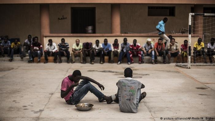 A migrant finishes his lunch while others wait to return to their barracks at a Libyan detentioin center for migrants