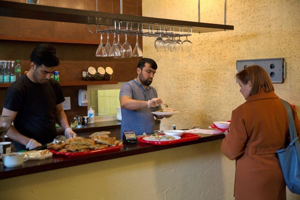 Sulaymon et Mohammad font la connaissance d'autres habitants de la ville qui viennent manger dans leur restaurant | Crédit : Zivilé Raskauskaite