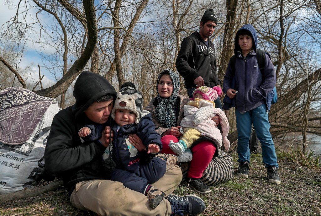 A group of migrants with children resting on the bank of the Meric Evros River at the Turkish-Greek border near Edirne Turkey  Photo EPASedat Suna