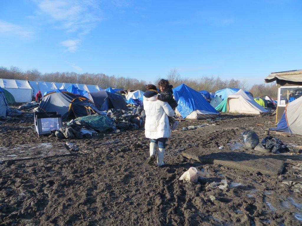 هما تحمل ابنتها جنا عبر الوحول المحيطة في الخيم بمخيم غراند سينث شمال فرنسا. الصورة التقطت عام 2015. مهاجر نيوز
