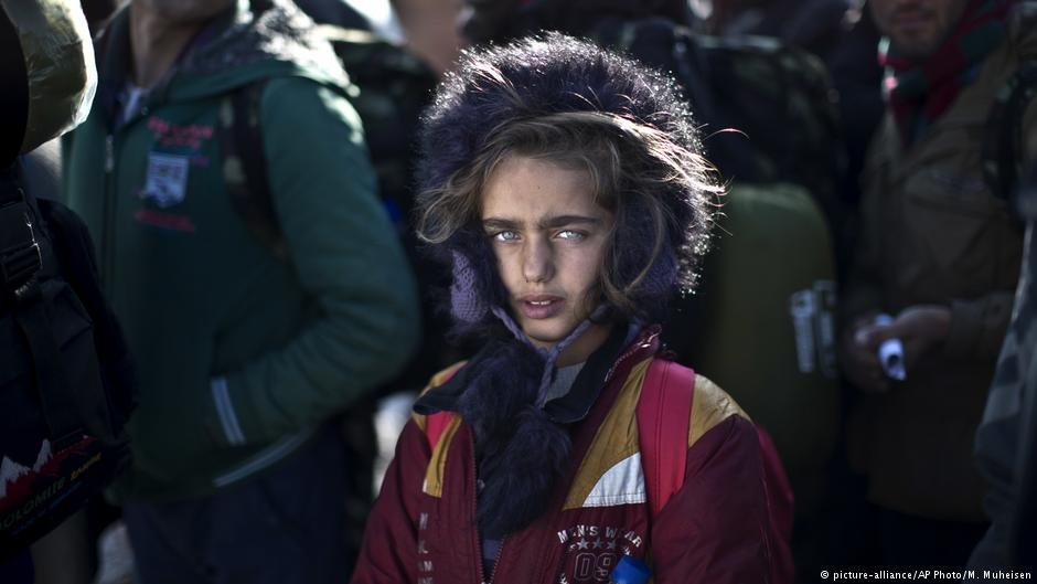Yazidi refugee Salma Bakir, 9, from Iraq, waits with her family to be permitted by Macedonian police to board a train heading to the Serbian border | picture-alliance/AP Photo/M. Muheisen
