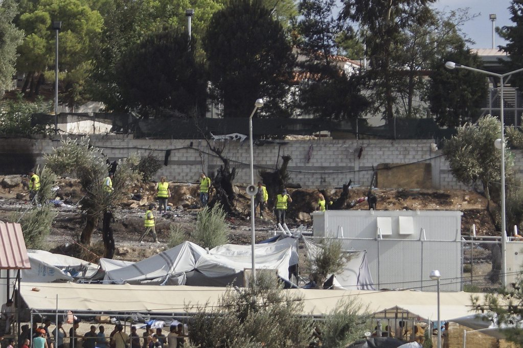Workers cleaning up the camp of Moria following clashes between groups of refugees and migrants of different nationalities Photo: EPA
