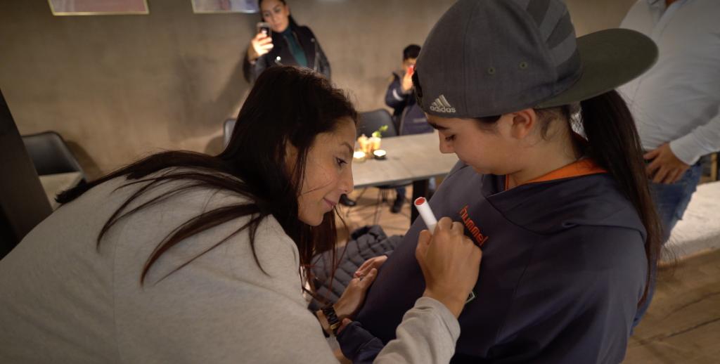 Nadia Nadim signs a football jersey for a young girl, Helin Kanbul   Photo: Claudia Jardim