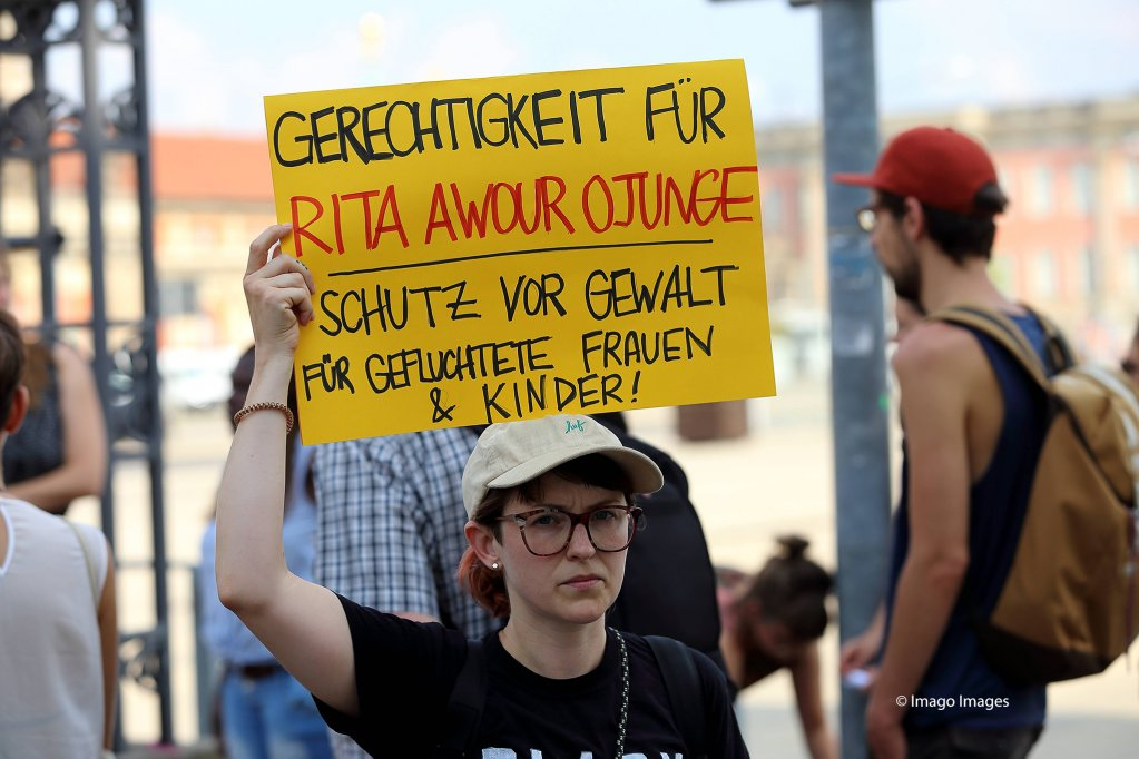 """This protestor demands: """"Justice for Rita Awour Ojunge"""" and """"Protect refugee women and children from violence"""""""