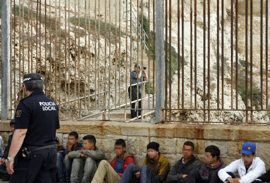 A Spanish National Police member and a Civil Guard watch some of the 70 sub-Saharan migrants, of whom 61 were reportedly minors, at the border of Ceuta-Melilla Photo: EPA