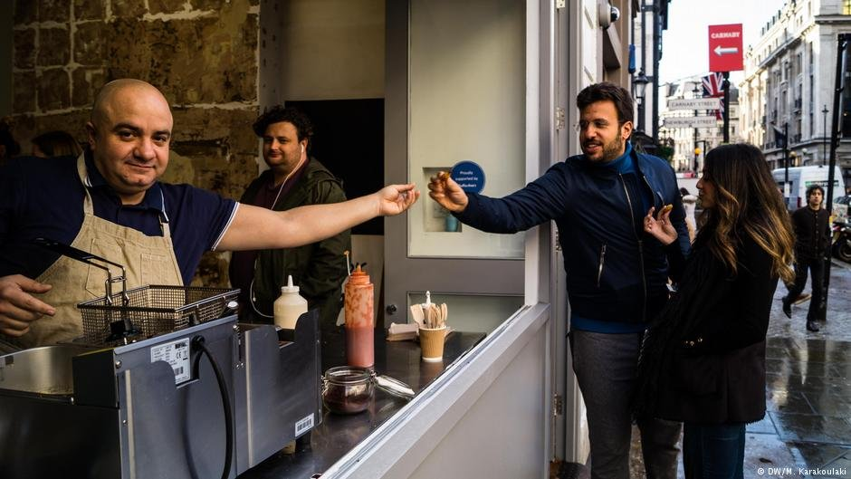 Imad Alarnab hands  a falafel to a couple who walk by his pop-up restaurant | Photo: DW/M. Karakoulaki