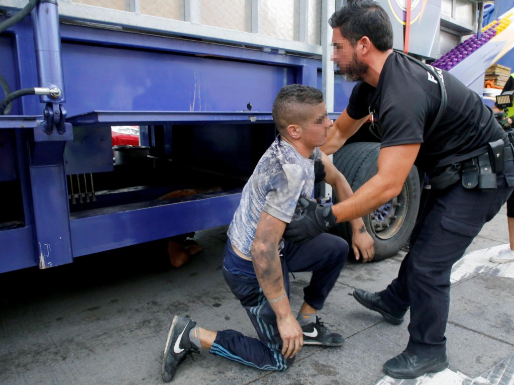 A Spanish National Police agent discovers a young man as he searches one truck at the end of a local holiday in Melilla, Spanish enclave in northern Africa Credit: EPA/F.G. Guerrero Editors note: Face of policeman and minor blurred by source in accordance with Spanish law
