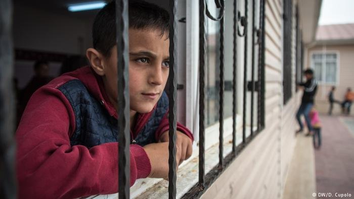A boy looks out from a school in Nizip 2 refugee camp in southern Turkey