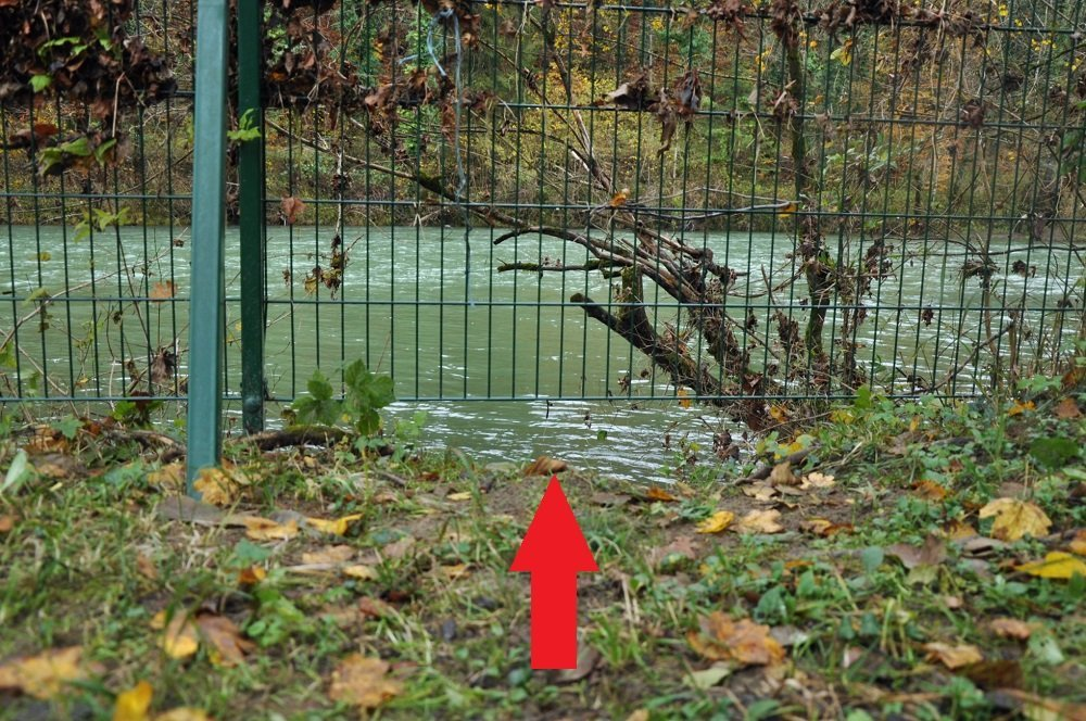 As the river level fluctuates, gaps appear under the fence. Credit: InfoMigrants
