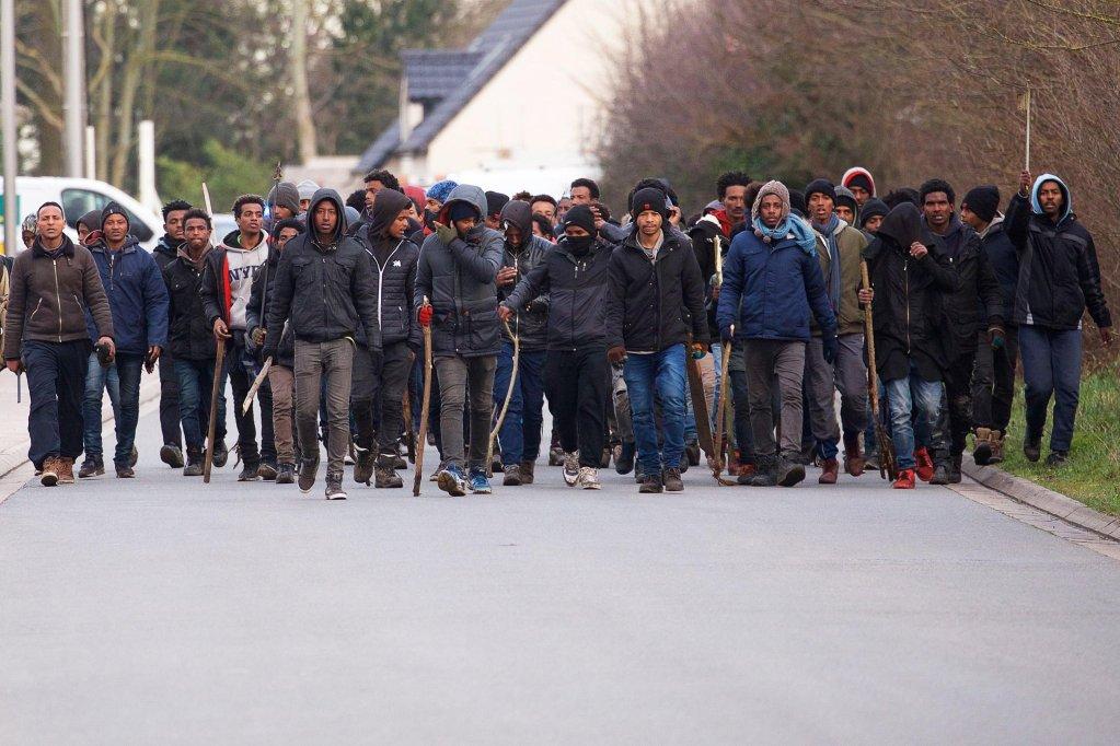 """ansa / مجموعة من المهاجرين يحملون العصي خلال اشتباكات قرب ميناء العبارات في كاليه. المصدر: """"إي بي إيه"""" / جون بن عزوز."""