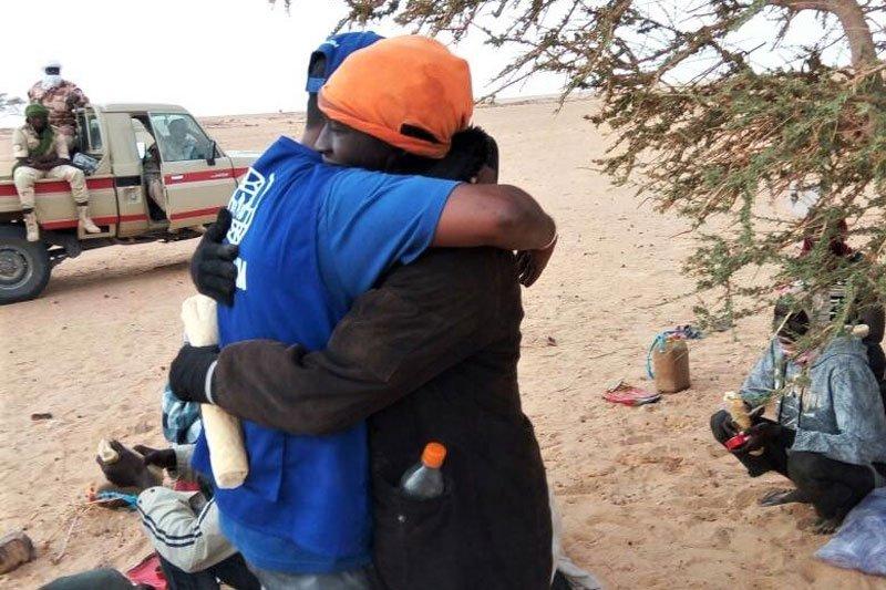 Un sauveteur de l'OIM serre dans ses bras un migrant secouru dans le désert de Ténéré. Une vingtaine de Gambiens et de Sénégalais ont été sauvés lors de cette opération. Crédits : OIM
