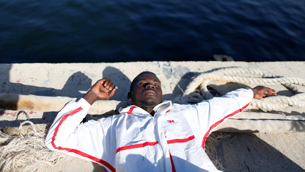 Un migrant exténué dans le port de Tripoli, en Libye. Crédit : Reuters